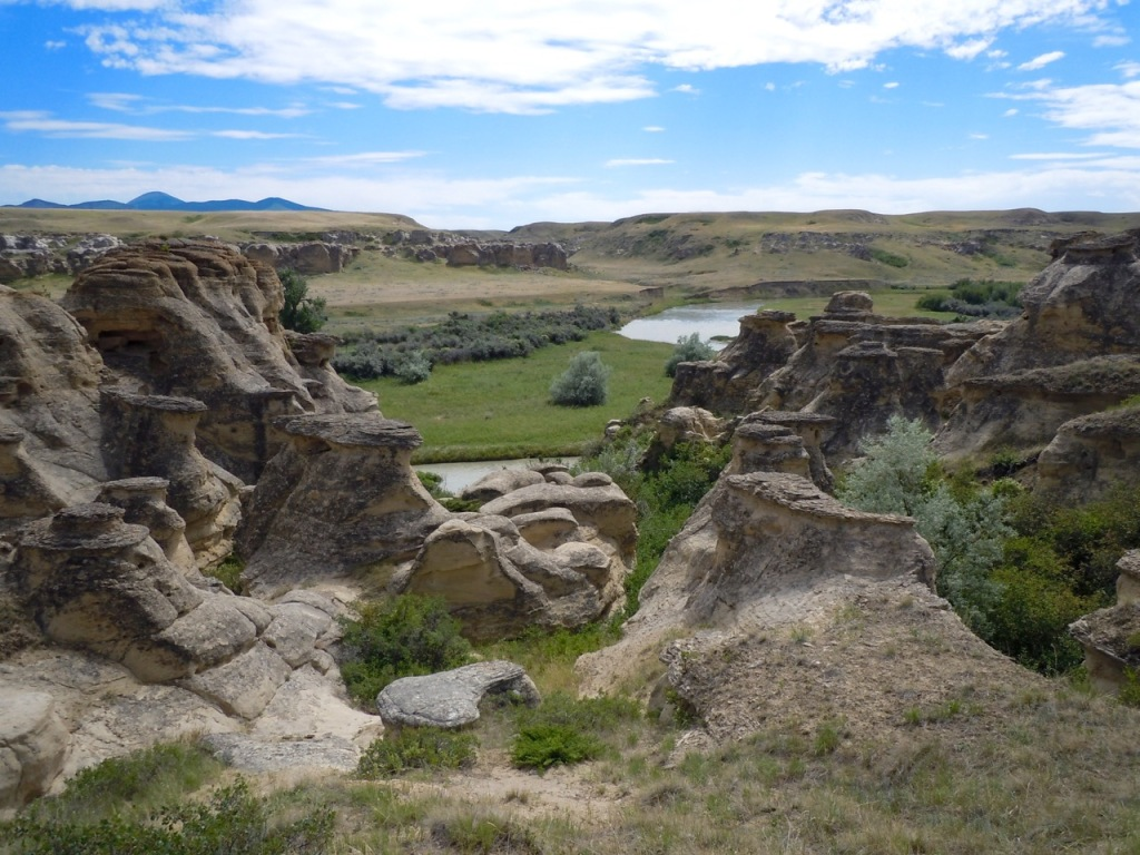 In the foreground are hoodoos along the Milk River valley in the midground. The opening of a coulee is in the centre of the image, just above the Milk River, with the Sweetgrass Hills in the background on the left.